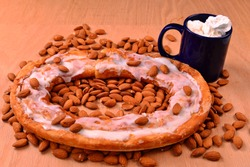Almond Kringle on a bed of almonds laid over an red oak surface with a cup of hot chocolate.