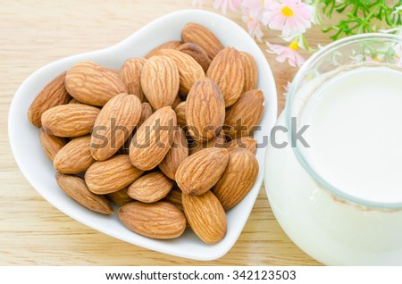 Almond milk with almond on a white bowl cup with flower on sack background.