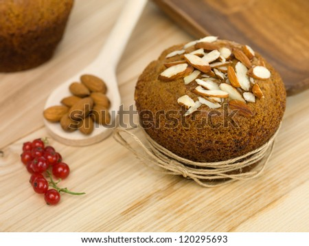 almond muffin, on a wooden table, with a wooden spoon beside it and a bunch of almonds and redcurrants