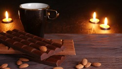 Almond nuts and a pile of three tiles of black and milk chocolate on a wooden background with a large dark cup and burning candles in the blurry background with selective focus.