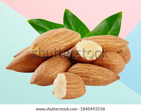 Almond nuts with three green leaves isolated
