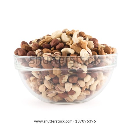 Almond, pistachio, peanut, walnut, hazelnut mixed in a glass bowl isolated over white background