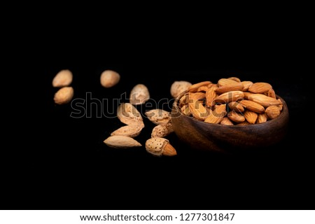 Almonds. Almond core beans in wooden cup. Almond dark concept photo with copyspace area. #1277301847