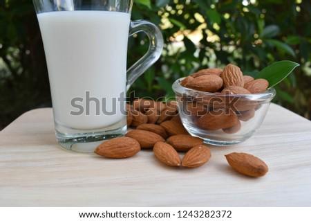 Almonds, almonds, almonds, wooden table alms, almond milk, almonds in a glass bowl. #1243282372