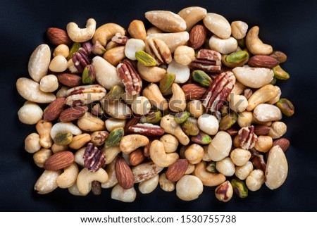 Almonds,Cashews,Macadamias,Pistachios,Brazil Nuts,Hazel nuts,Pecans isolated on black Background close up.