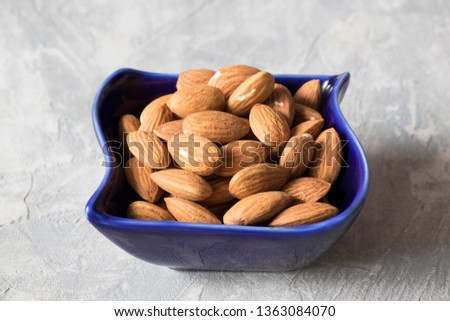 almonds in a blue bowl on the table, healthy food concept
