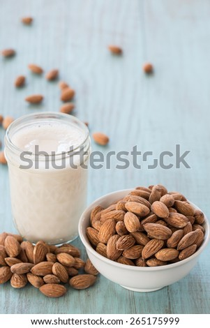 Almonds in white bowl on blue wood background with glass of almond milk vertical