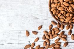 Almonds in wooden bowl on wihte background.