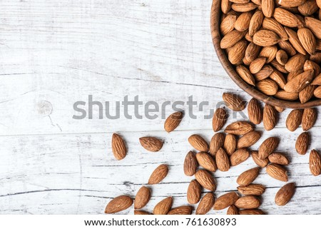 Almonds in wooden bowl on wihte background. #761630893