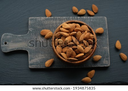 Almonds nuts  in a round wooden cup on a black shabby chic board on a black schiffer  background.Nuts and seeds. .Healthy fats.Heap Almonds shelled  nut closeup.Tasty organic snack