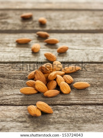 Almonds nuts on an old vintage planked wood table - rustic style image