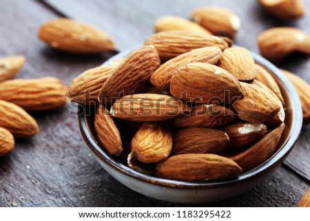Almonds on a rustic wooden table and almond in bowl #1183295422