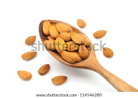 almonds on white fund with a wooden spoon