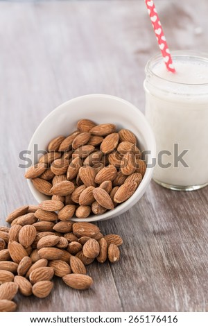Almonds spilling out of white bowl onto wood background with glass of almond milk with heart straw