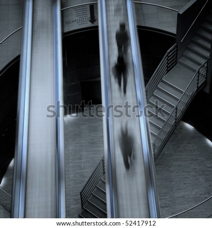 Almost abstract composition of moving stairs crossing the interior of the Royal Library in Copenhagen with people moving on and being blurred
