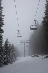 Almost empty Ski Lift on a snowy winter landscape, with snow covered mountains and big pine and fir trees, in the fog. The chairlift has no people on it.