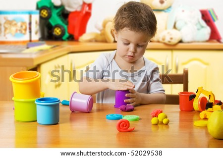 Almost 2 years old child playing plasticine in children's room
