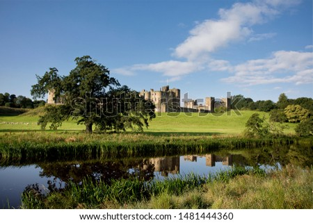Alnwick Castle in Northumberland and is pictured here reflected in the River Aln on a bright August morning. The castle dates from 1096 and is more recently featured in the Harry Potter films
