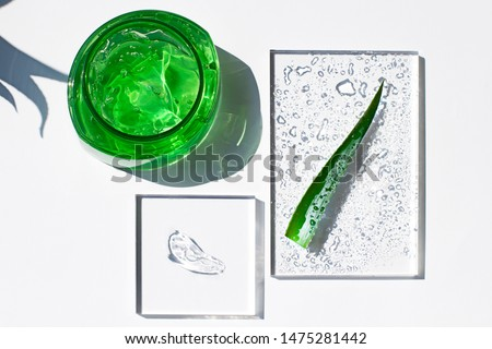 Aloe vera fresh gel in a plastic bottle flat lay with  a smear of transparent gel and a leaf. After sun cooling skin cosmetics top view