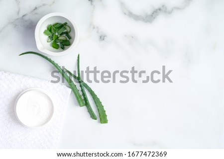 Aloe vera natural organic cosmetic cream moisturizer and sliced stems aloe vera on marble background. Flat lay, top view. Beauty product for face and hand skincare