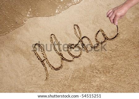 Aloha text handwritten in sand on a beautiful beach