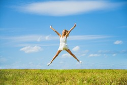 Alone blond Woman Jumping for Joy on a Grass Hill above horizon line One happy slim girl fly in a green field against blue summer sky with clouds Idea of success, growth , light, diet, luck, freedom