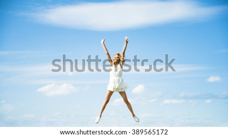Alone blond Woman Jumping for Joy on a Grass Hill above horizon line One happy slim girl fly in a green field against blue summer sky with clouds Idea of success, growth , light, diet, luck, freedom #389565172