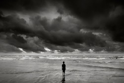 alone boy near the beach with dramatic stormy sky   during monsoon season