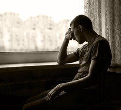 Alone broken sullen young teen guy person sit waiting look on light white gloomy city copyspace in window. Male addiction psychological emotion portrait and space for text on dark home room background
