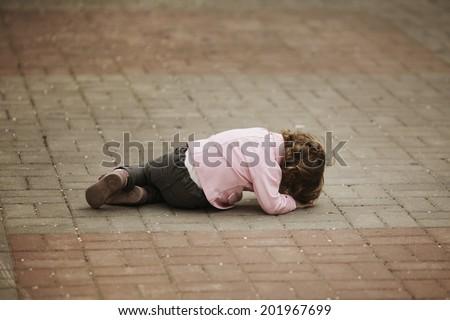 alone crying girl lying on asphalt