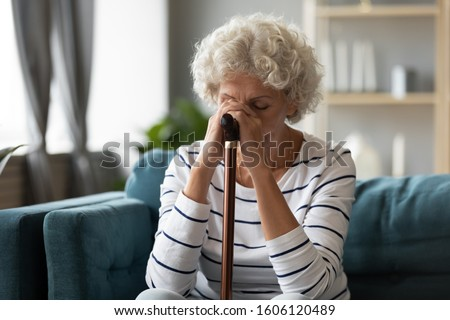 Alone disappointed upset 70s woman sitting on sofa hides her face with hands holding walking stick suffers from physical disability disease movement difficulties, need caretaker social problem concept