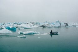 Alone fisherman driving boat in calm water of Diamond Beach in Iceland. Floating big blue glacier ice blocks on sea surface. Arctic Adventures in Jokulsarlon Iceberg Lagoon. Low contrast photo.