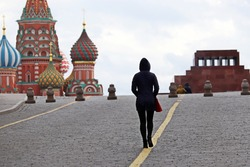 Alone girl tourist walking on Red square in Moscow on background of St. Basil's Cathedral and Lenin's Mausoleum. Empty streets during the coronavirus pandemic in Russia