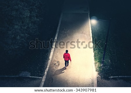 alone girl walking in the park in the night