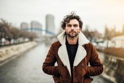 alone handsome man with beard and winter or autumn coat standing outside next to a river and thinking about something or waiting for someone