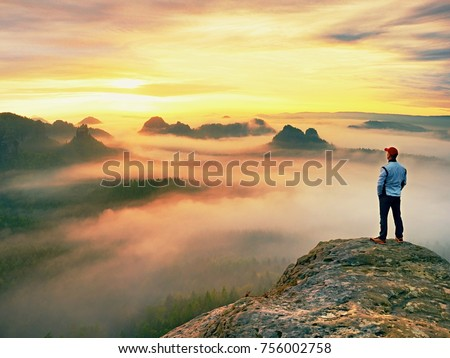 Alone hiker in red cap stand on peak of sandstone rock in rock empires park and watching over the misty and foggy morning valley to Sun. Beautiful moment the miracle of nature  #756002758