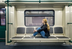 Alone in the subway. A blonde woman sitting in subway train and looking at window