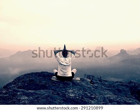 Alone man is doing Yoga pose on the rocks peak within misty morning