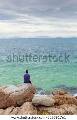 Alone man (lonely) on the rock beside the sea