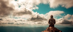 alone man sitting on the peak of mountain cloudy sky lonely scene, waiting for hope, landscape panorama view, copy space