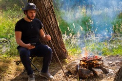 Alone man sitting on the stool in front of the brook. Man sitting near the camp fire. Guy having a barbecue in nature. Someone making shish kebab. Young dude making barbecue. Barbecue outdoors.