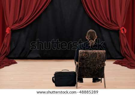 Alone man sitting turn back at stage with red drapery - stock photo