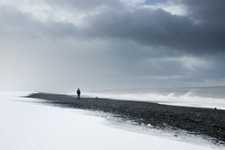 Alone man standing on the dark nordic beach in Iceland - thinking, loneliness concept photo