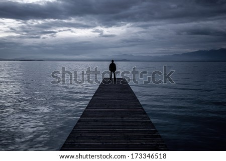 Alone man standing on the edge of a pier in twilight