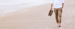 Alone man walking on the beach carrying leather shoes, lifestyle and travel concept, banner style for text