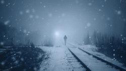 Alone man walks along a railway track in a heavy snowfall to meet a train . Misty mystical road. Film toning