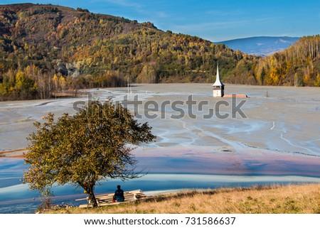 Alone on the polluted lake shore, Geamana, near Rosia Montana, Carpathian mountains Romania. man sitting under the apple tree, submerged church #731586637