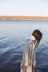 Alone sad girl in beige rain trench coat, white hoody standing on stone pier of waterfront with river on background. Side view of alone young girl standing on the beach and look at water.