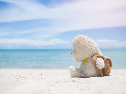 Alone teddy bear sitting on sand beach with blur blue sea and blue sky. for valentine days, broken heart, travel summer in holidays. Communicate to travel alone and no boyfriend, not frend. lonely.