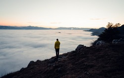 Alone tourist in rocky mountains. Hiker stand on rocky view point above misty valley. Shrouded in mist and clouds with the peak visible. Scenic landscape photo composite. Adventure, Explore, Hike,